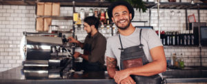 Coffee shop worker smiling to camera